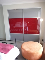 Set of two wardrobe doors in a bedroom with three panels, the middle panels red and the top and bottom panels silver