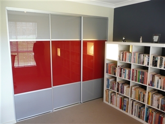 A bedroom with a bookcase, which has a set of three doors, the middle panel red and the top and bottom panels silver