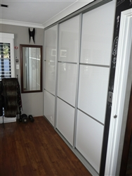 Three artic white sliding doors with three panels each. In a bedroom with floorboards and a mirror on the wall