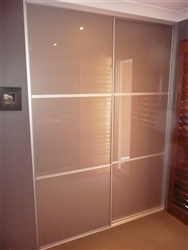 A set of two sliding doors in a room with three panels, all panels are the colour champagne. This door design is called Trio