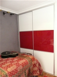 A bedroom with a bed and guitar, the sliding wardrobe doors have three panels,  top and bottom panels arctic and middle red