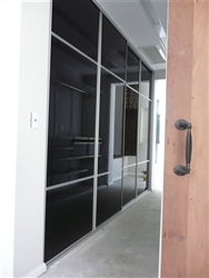 Four sliding doors in a hallway. Three panels that are phantom black. The middle panel is larger than the top and bottom